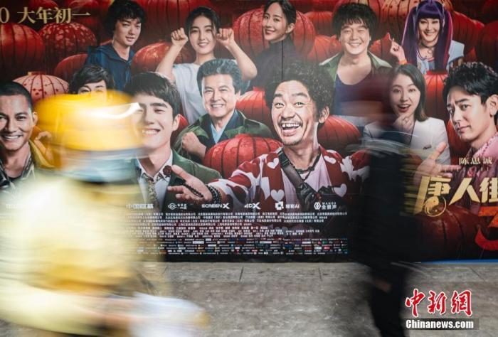 资料图:行人经过位于北京市朝阳区望京地区的一家电影院的户外广告。/p中新社记者 侯宇 摄