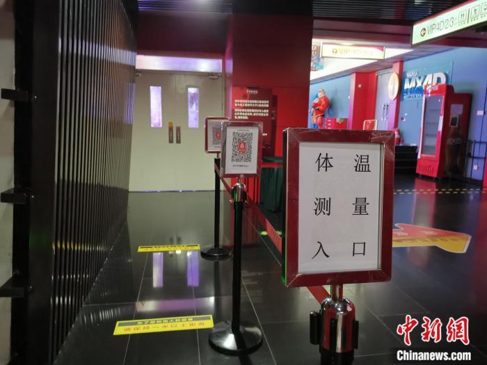 """7月23日晚,首都电影院西单店,入口通道已设置""""体温测量入口""""及北京健康宝指示牌。/p中新网任思雨 摄"""