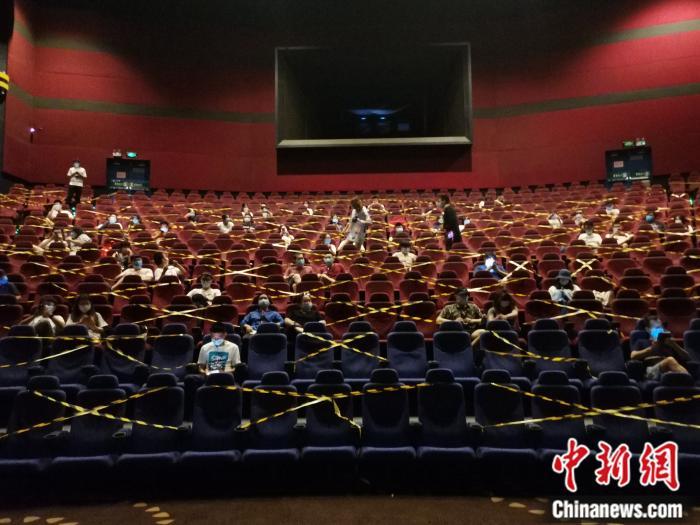 7月24日凌晨,万达影城石景山万达广场店,观众戴口罩分隔而座,等待零点场开始。/p中新网任思雨 摄