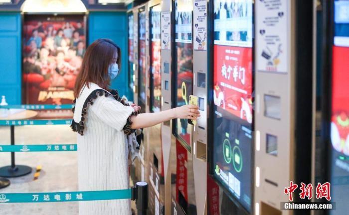 资料图:7月24日,观众在北京万达影城CBD店内自助扫码取票。/p中新社记者 贾天勇 摄