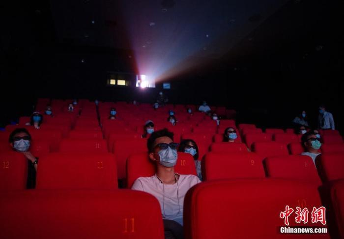 资料图:今年7月,位于北京市朝阳区的一家电影院内,观众间隔入座、佩戴口罩观看影片。/p中新社记者 侯宇 摄
