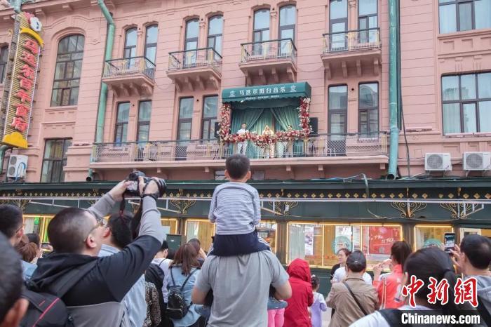 游客欣赏马迭尔阳台音乐 吕品 摄